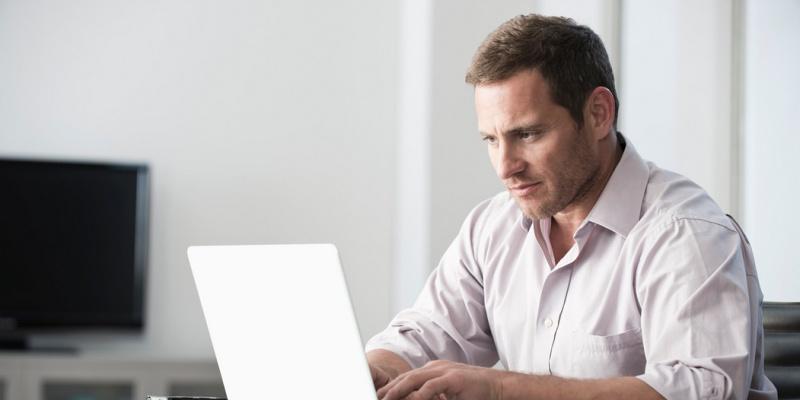 Un homme est assis devant un ordinateur et regarde les meilleurs sites de rencontres
